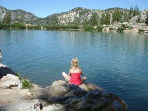child meditating by lake - wholesome living